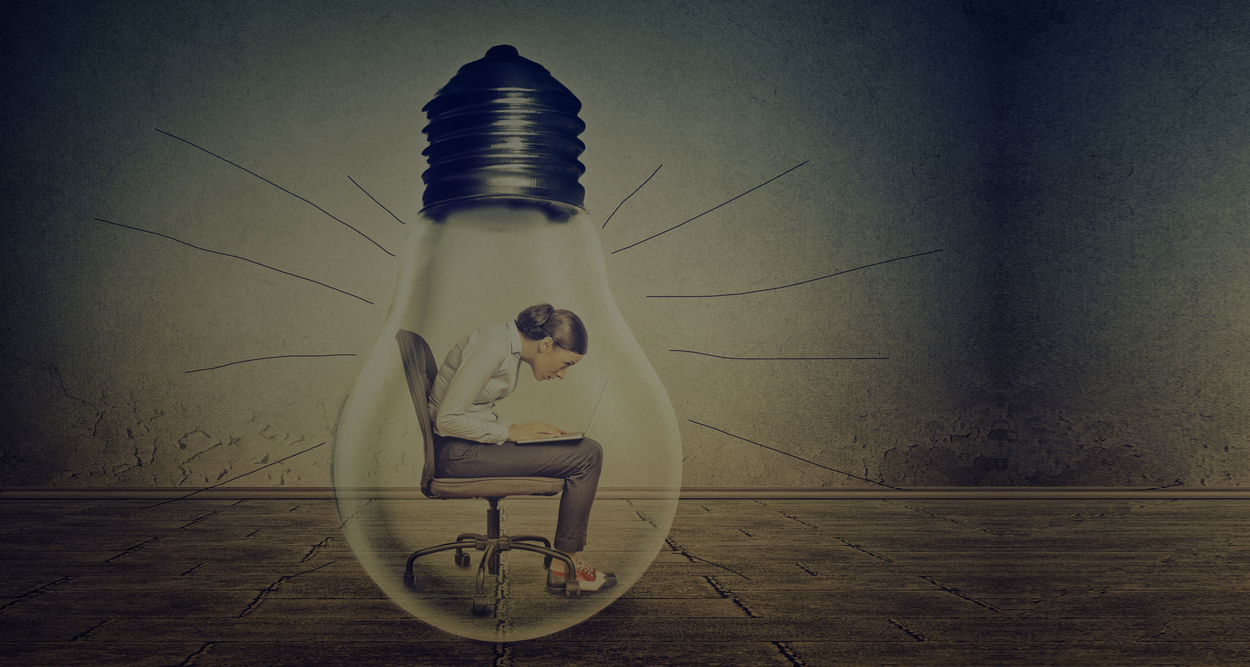 Woman working on laptop computer sitting inside electric light bulb isolated on gray office wall background2 copy-1